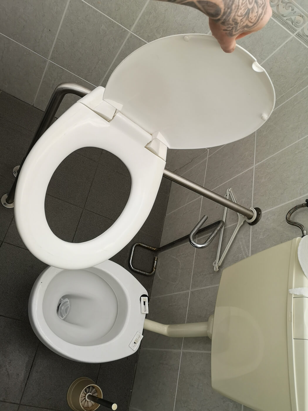 A mans hand can be seen holding a toilet seat which has completely broken from the toilet at Cordoaria Nacional in Lisbon