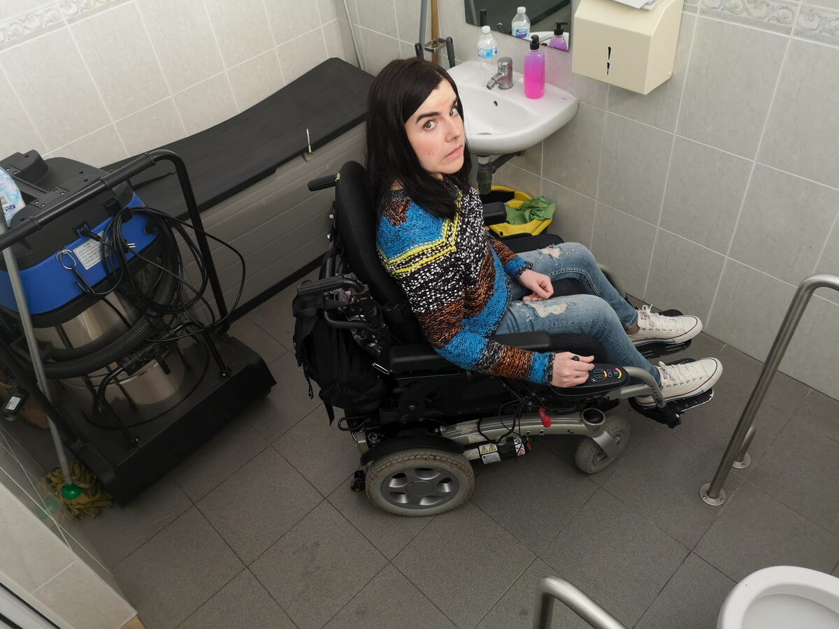 Emma sitting in her wheelchair inside the disabled toilet at Cordoaria Nacional in Lisbon