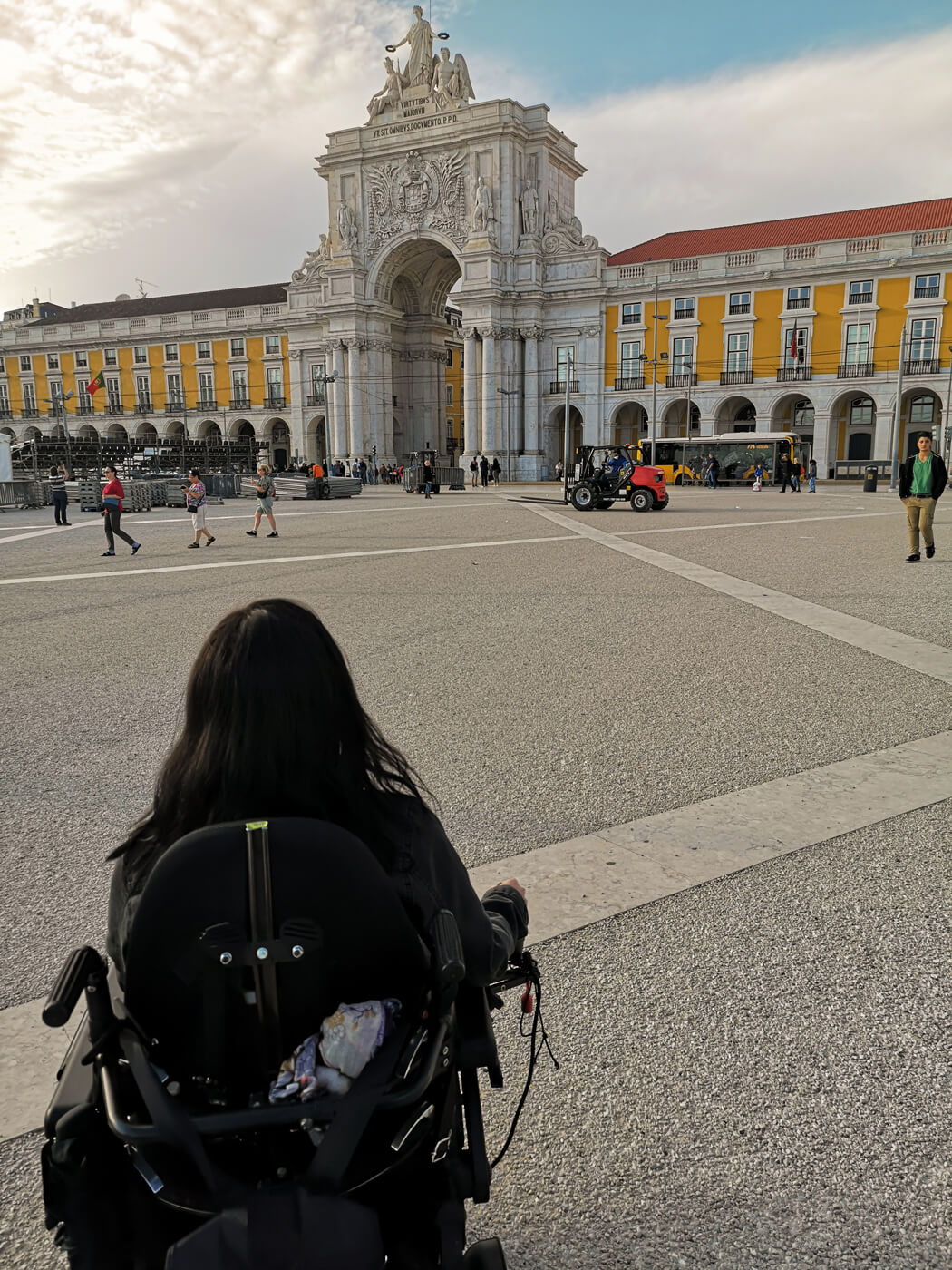 A view of Emma from behind driving her power wheelchair through Praça do Comércio in downtown Lisbon.