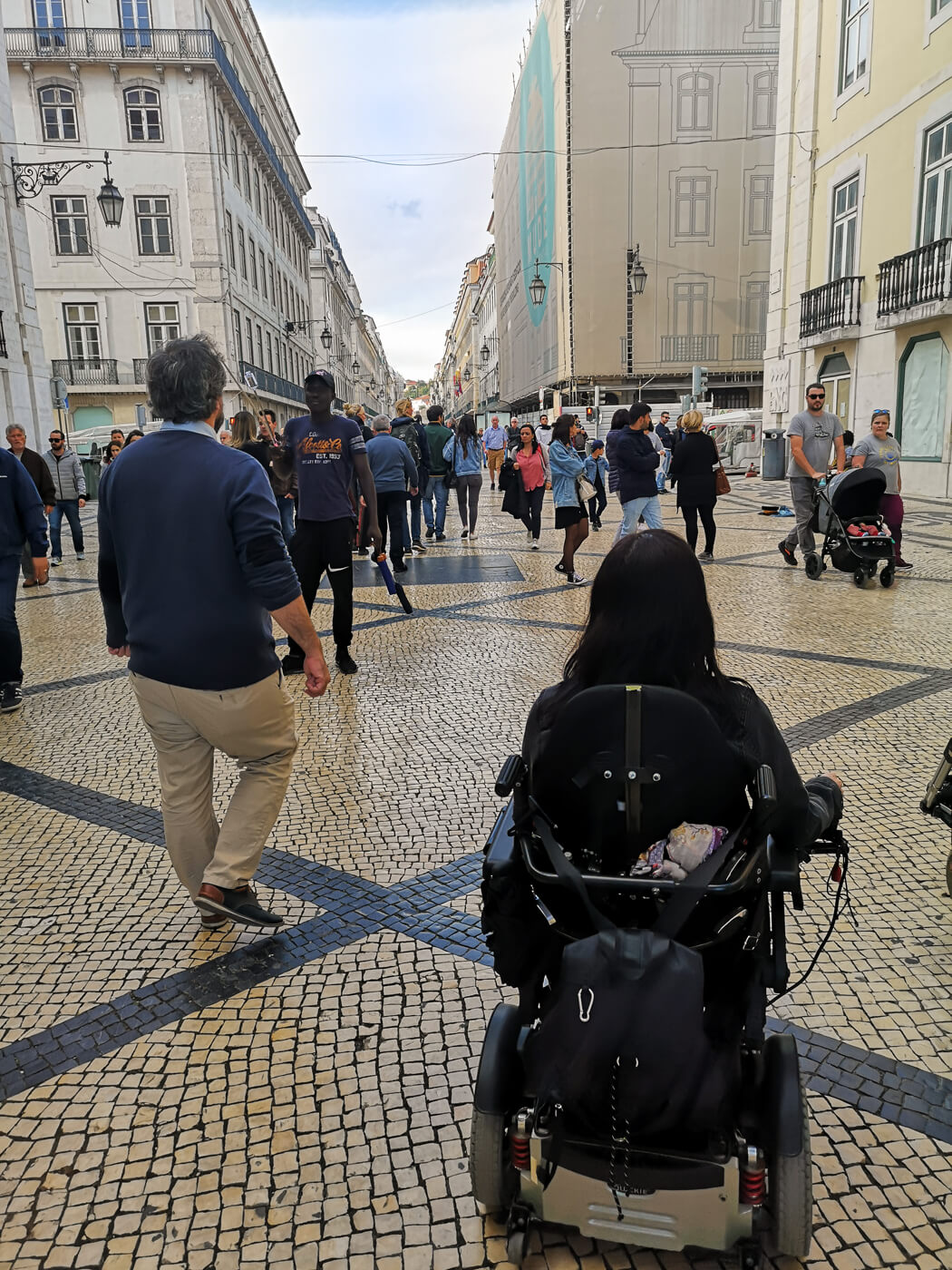 Emma in her wheelchair driving through a busy street in downtown Lisbon.