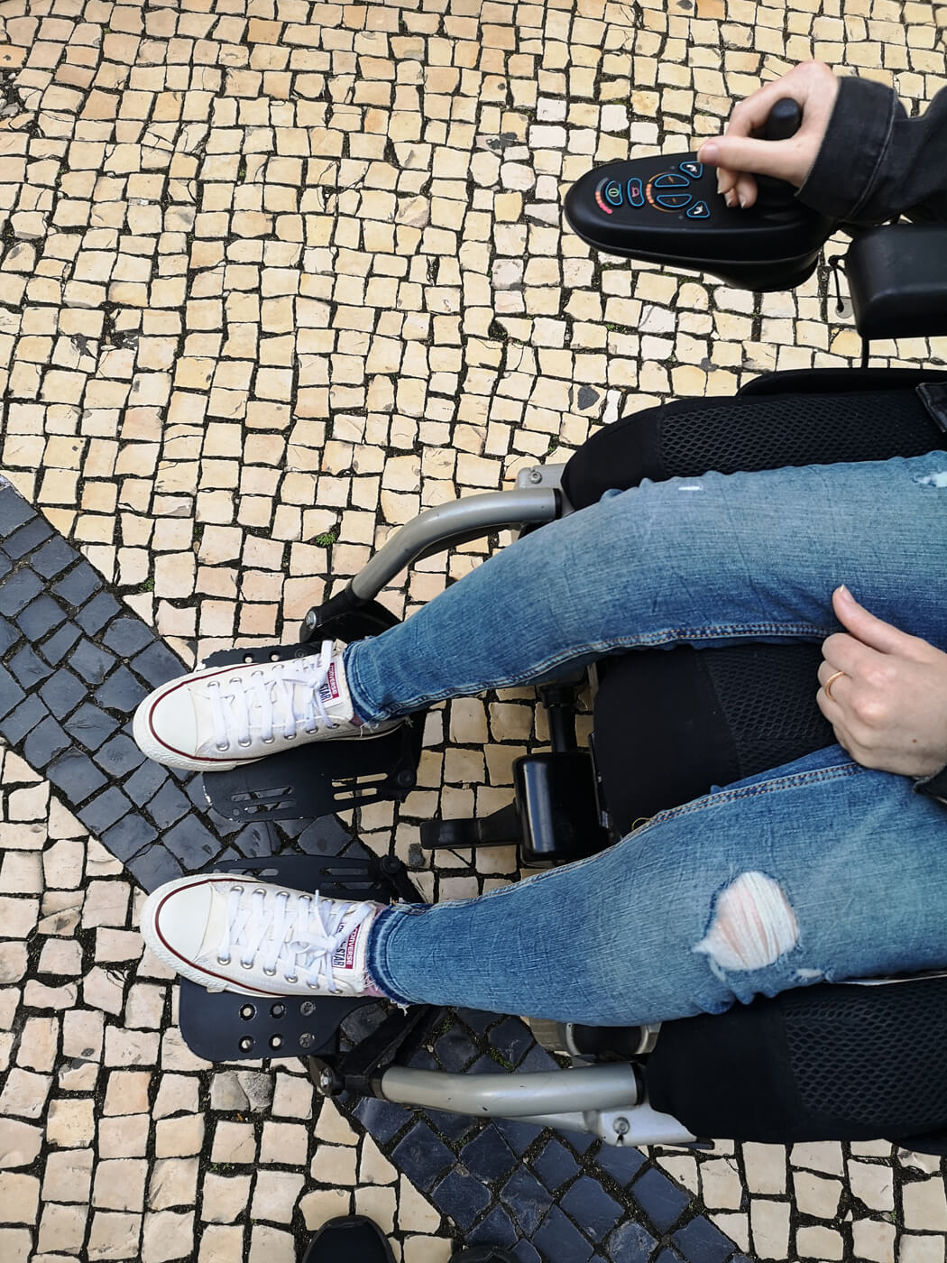 A view looking down at Emma's legs in her wheelchair and the tiled ground.
