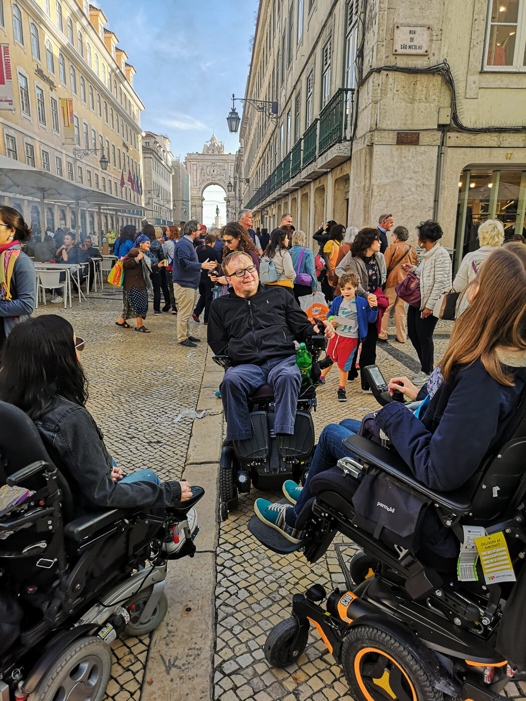 Emma, John and Blandie, all wheelchair users sitting together talking in the middle of downtown Lisbon.