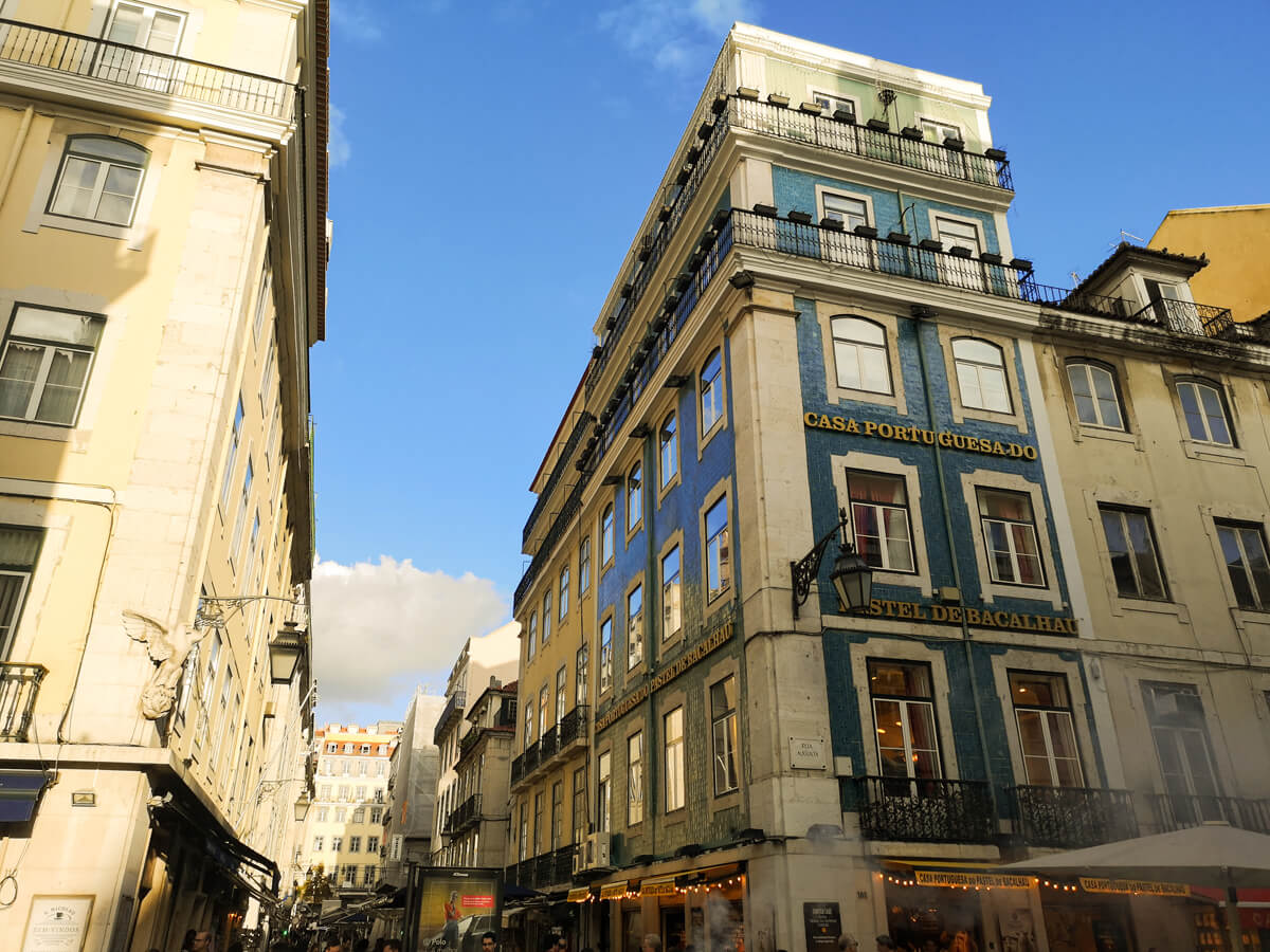 Casa Portu Guesa Do building in downtown Lisbon. Behind the building is a bright blue sky.