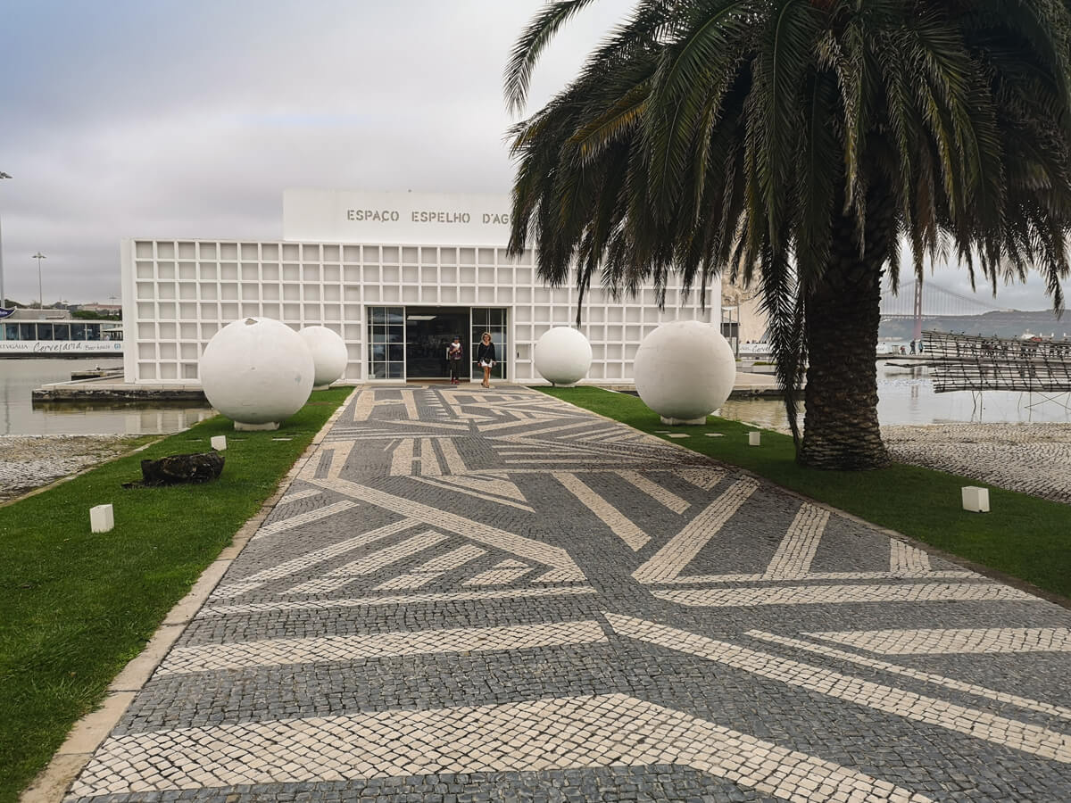 Exterior shot of Espaço Espelho d'Água restaurant in Lisbon. The Tagus River and 25 April Bridge are in view. A large palm tree is at the front of the restaurant.
