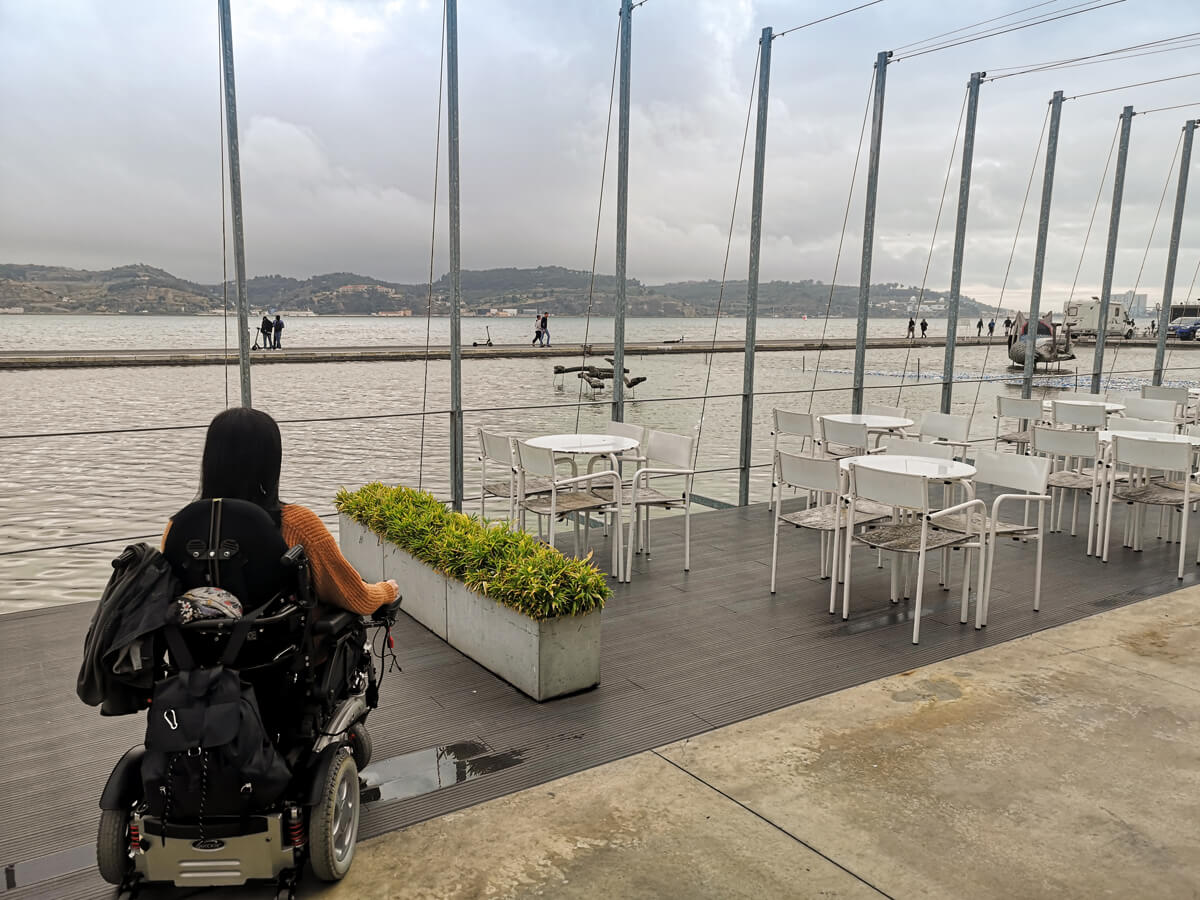 Emma has her back to the camera. She is sitting on the outdoor terrace looking out across the Tagus River.