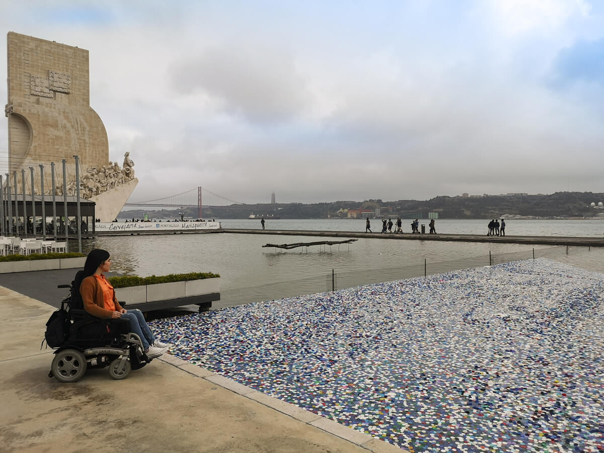 A side view of Emma sitting in her wheelchair. She is sitting on the outdoor terrace looking out across the Tagus River. The Belem Tower, Tagus River and 25 April Bridge are in the distance.