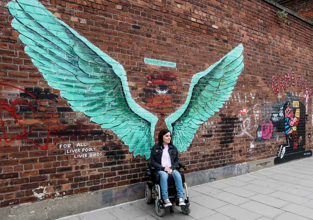 Emma sitting in her wheelchair against a brick wall. The wall has giant green angel wings spray painted on it by artist Paul Curtis. Emma has her wheelchair turned slightly away from the camera and she is looking off to the side.