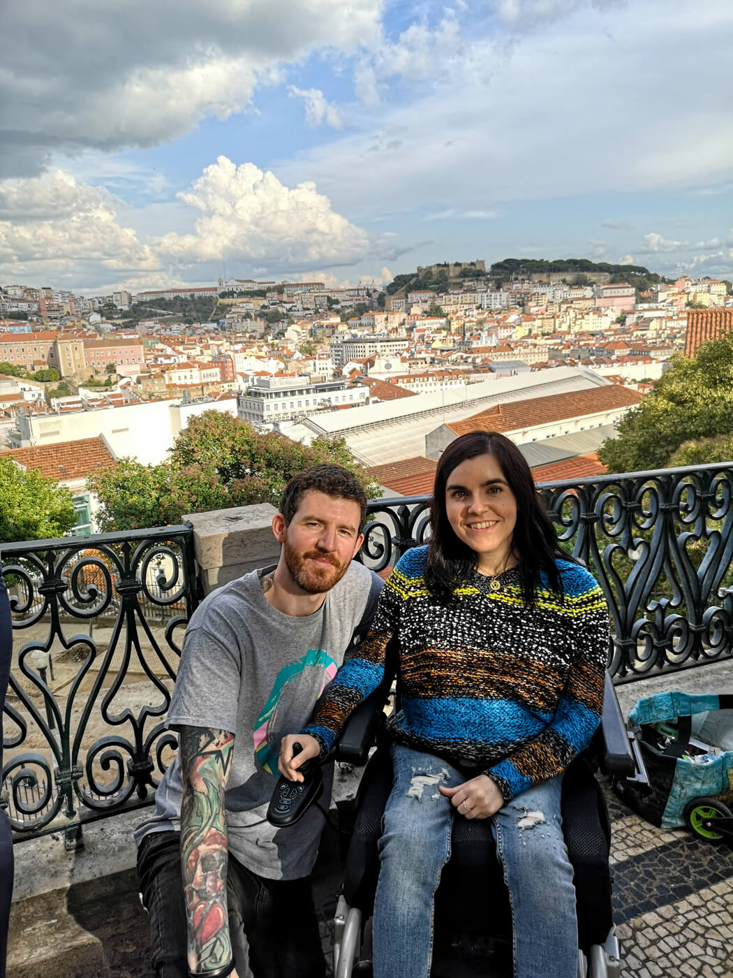 Emma sitting in her wheelchair with Allan, her partner kneeling beside her. They are smiling at the camera with the view of Lisbon city behind them while at the Jardim de São Pedro de Alcântara viewpoint in Lisbon