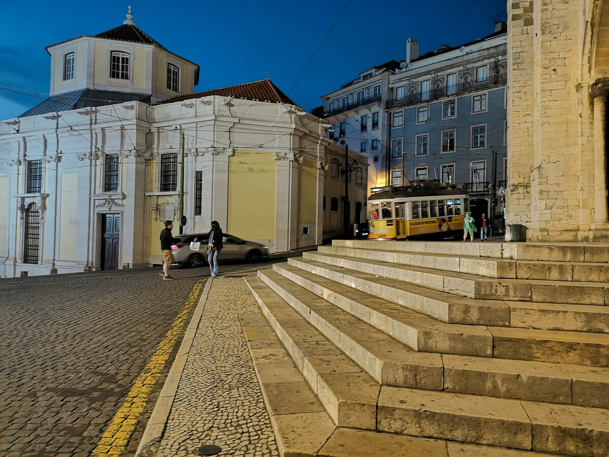 A yellow tram riding past Lisbon Cathedral at night in the Alfama District area.