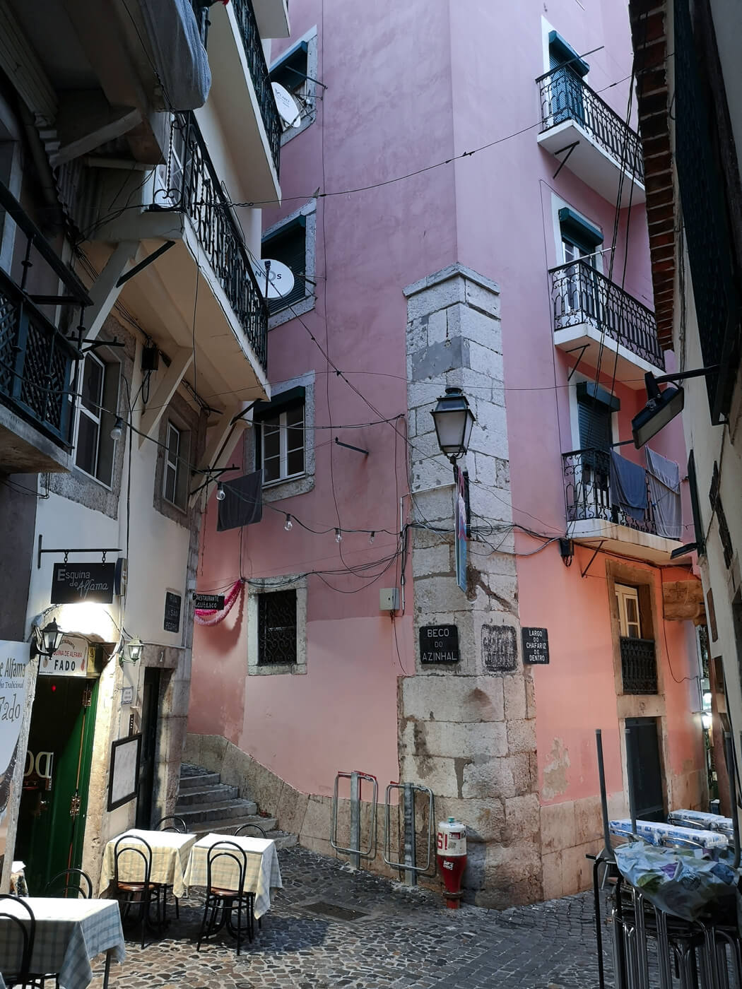 An old pink building in the old town Alfama district in Lisbon. There are tables and chairs set outside restaurants.
