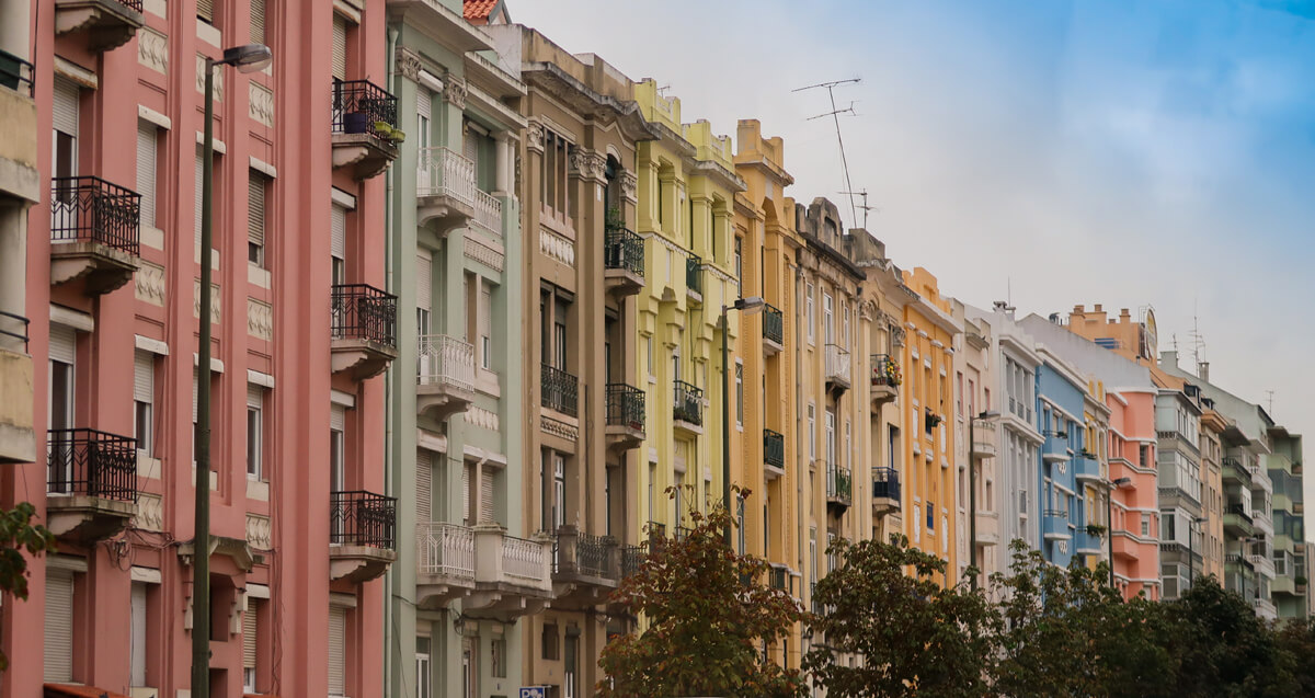 A row of bright colourful buildings in Lisbon, Portugal. Colours include pink, olive green, yellow, orange and blue.