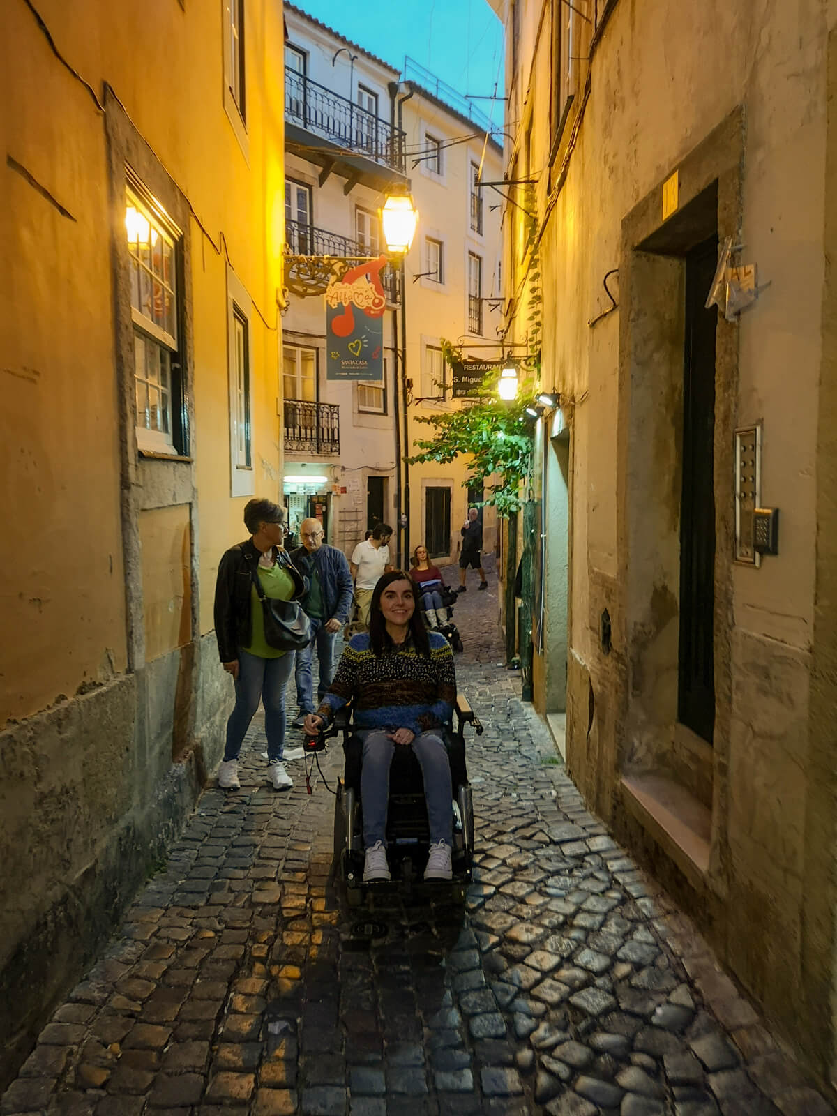 Emma driving her wheelchair over cobblestone streets in the old town Alfama district in Lisbon. Emma is wearing a multicolored top, blue skinny jeans and white converse shoes.