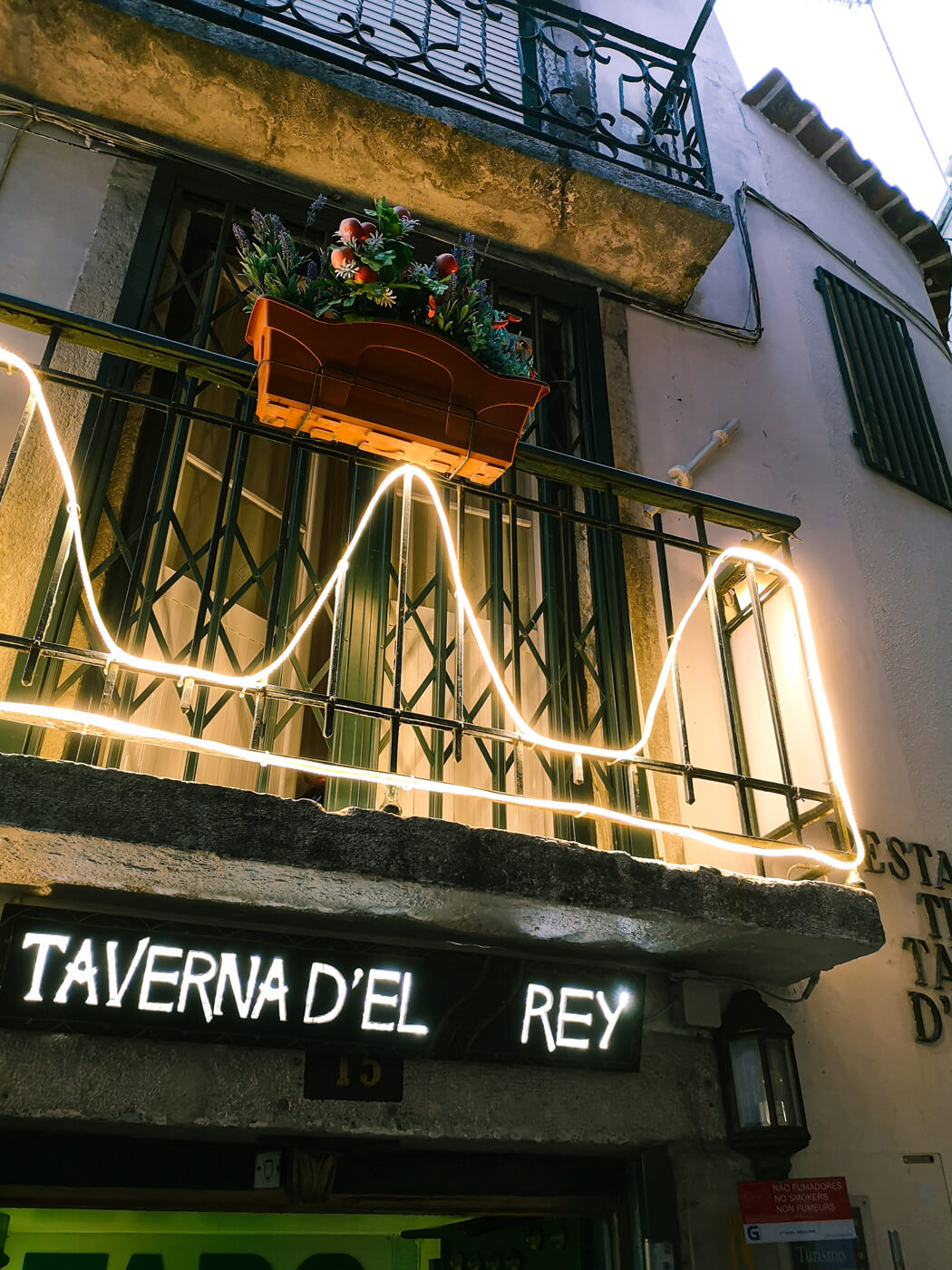 An exterior shot of a restaurant in the old town Lisbon area. A flower pot is hanging on the balcony and neon lights are drapped across. The pub sign is lit up and is called Taverna D'el Rey.