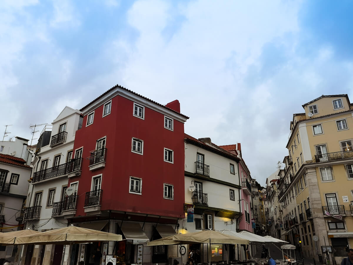 Colourful buildings in the old town Alfama district area. The restaurants have parasols up and people are sitting outside eating and drinking.