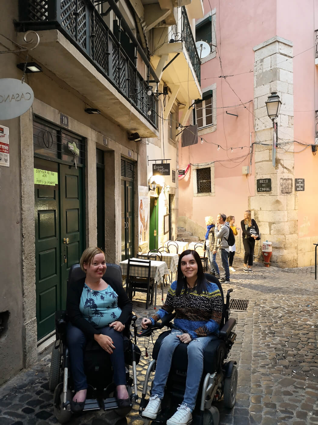 Emma and fellow wheelchair user Sanna sitting next to each other in the old town Alfama district Lisbon. Behind them is a pink old building and outdoor dining seating.