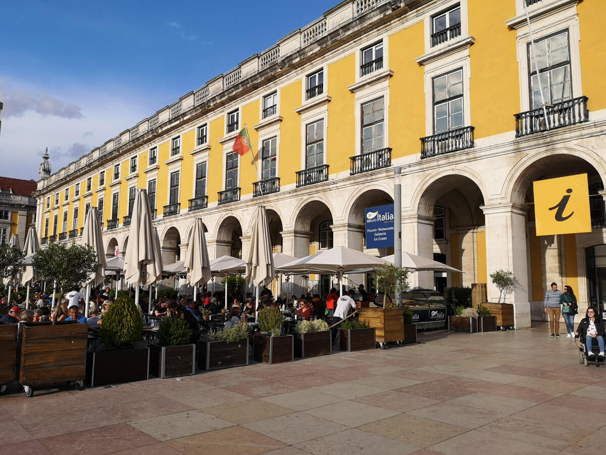 The exterior of Lisbon Story Centre, a large bright yellow building. There is an outdoor restaurant full of people and on the right of the photo, Emma is driving her wheelchair towards the camera.