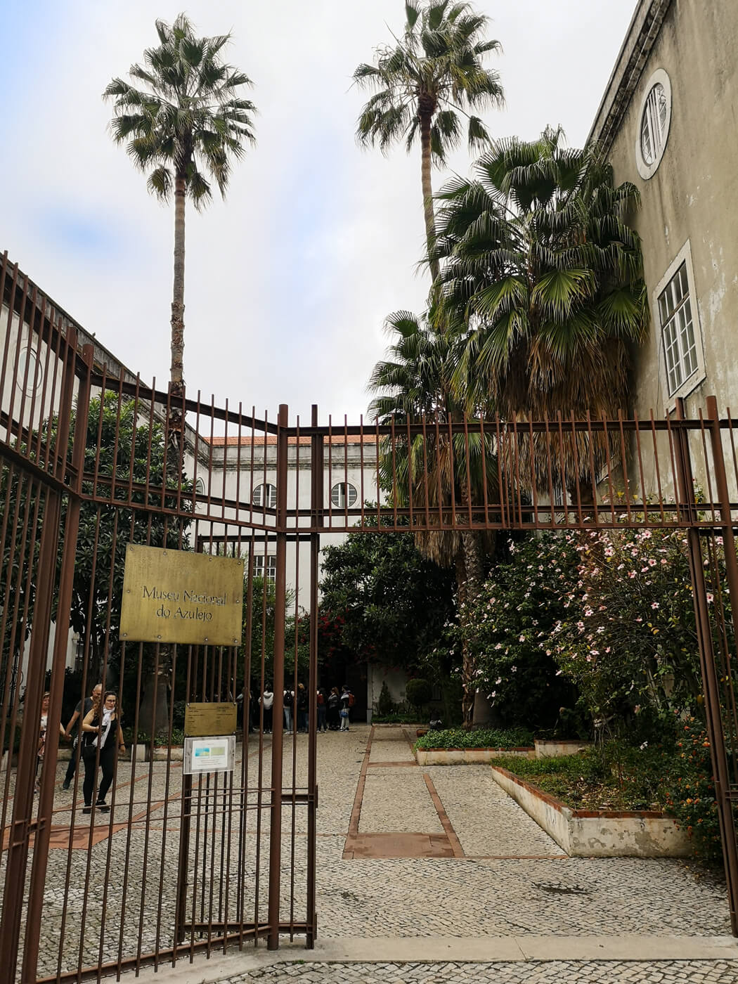 The entrance gates to the National Tile Museum in Lisbon. The courtyard is full of colourful plants and palm trees.