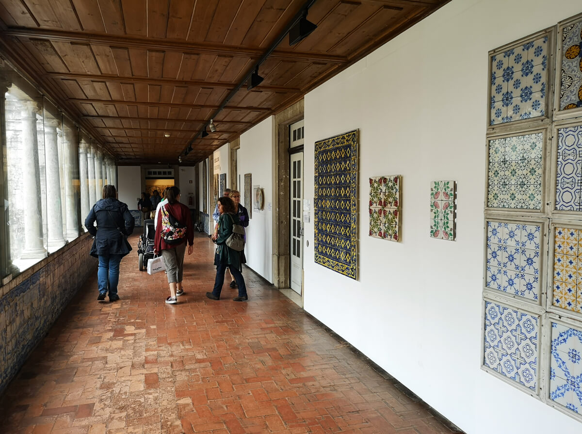 The hallway inside the National Tile Museum in Lisbon with tiles displayed on white walls. There are people walking with their backs to the camera.
