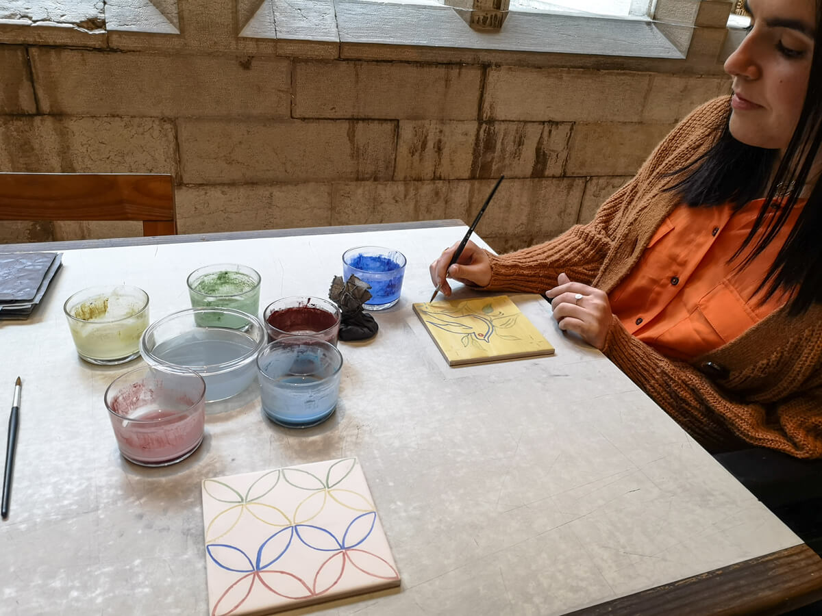 Emma sitting at a table painting her own tile at the National Tile Museum. There are glass bowls on the table with different colours of paint.