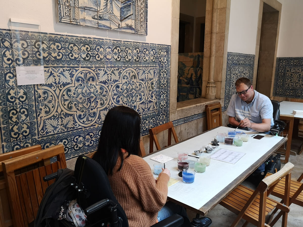 Emma and John from WheelchairTravel.Org sitting at a table painting tiles at the National Tile Museum in Lisbon