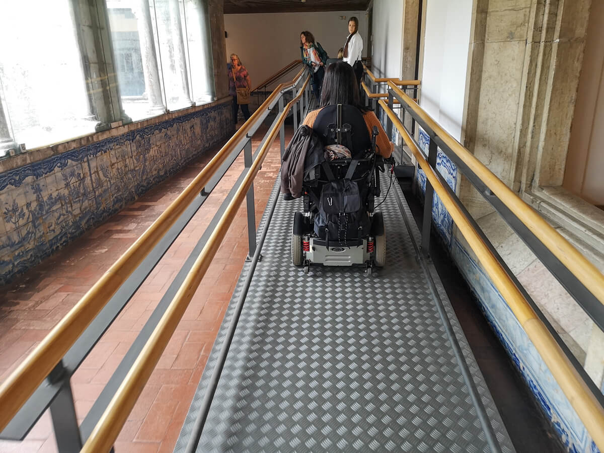 Emma driving her wheelchair up a portable metal ramp inside the National Tile Museum in Lisbon