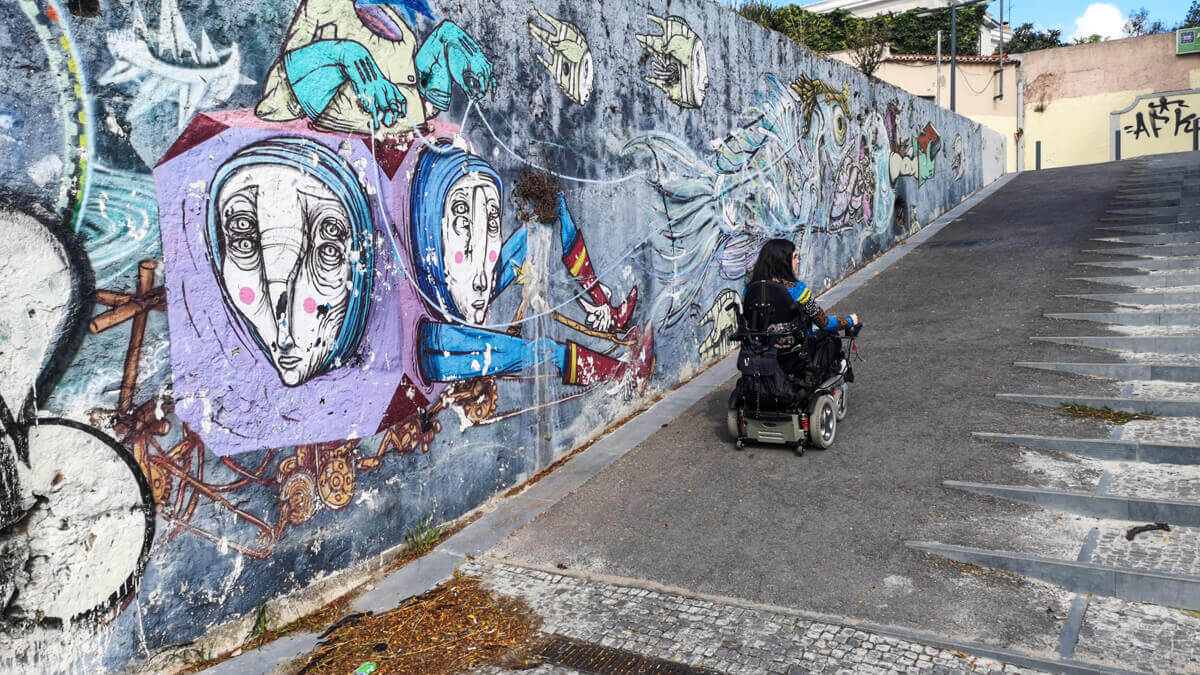 Emma driving up a steep concrete ramp alongside a wall covered in colourful graffiti in Riverfront of Belém's historic district