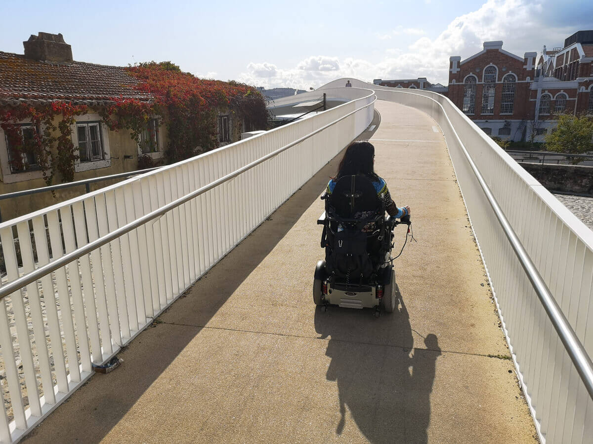 Emma driving her power wheelchair up a long over road bridge to get to the Riverfront of Belém's historic district.