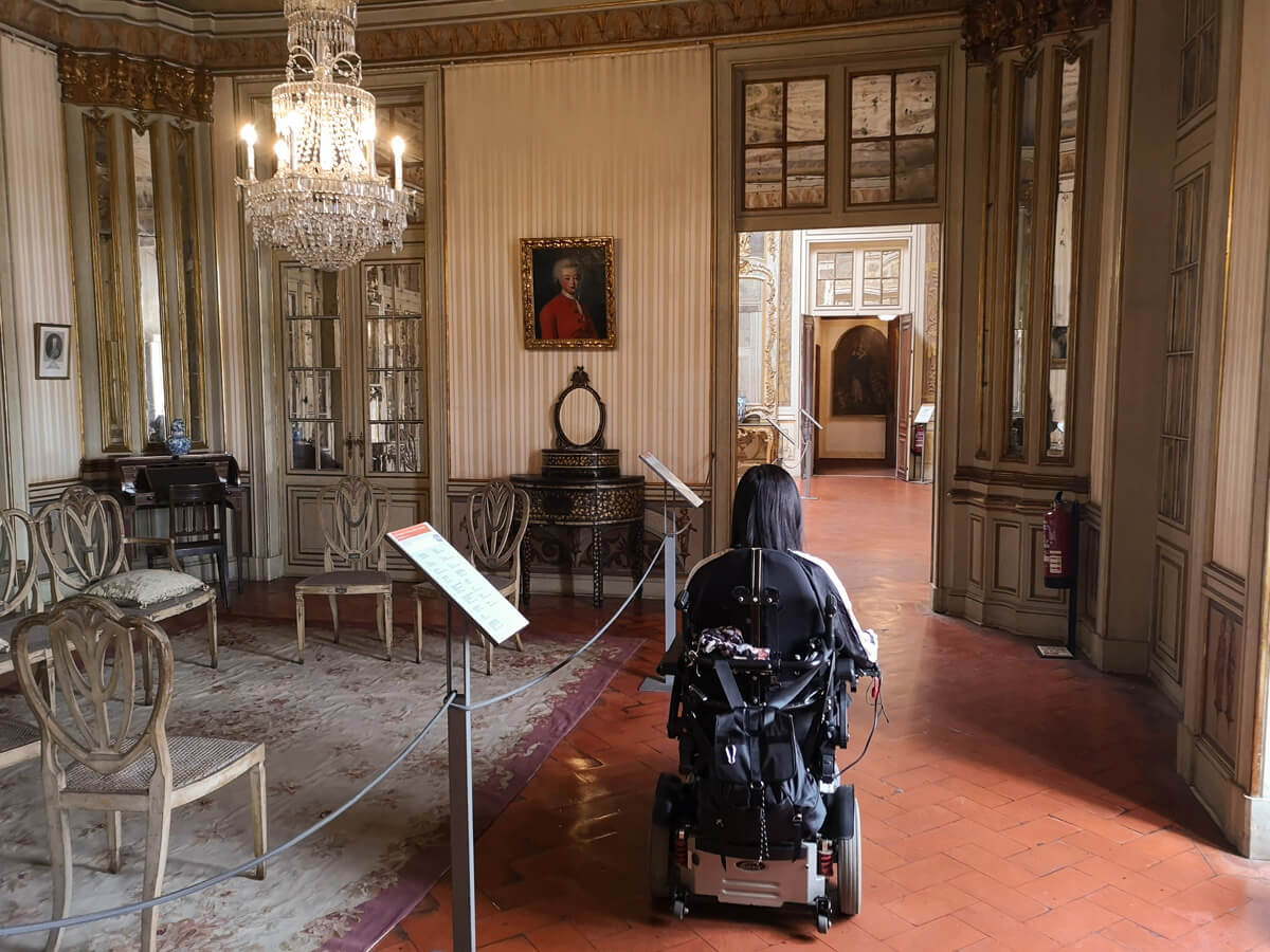 Emma has her back to the camera while driving her wheelchair through a room at Royal Palace of Queluz