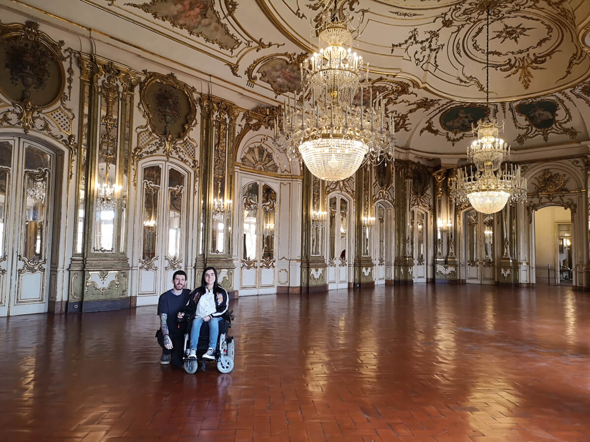 Emma, a wheelchair user and her partner who is kneeling next to her are smiling at the camera while in a massive royal room with beautiful chandeliers and gold painted ceiling.