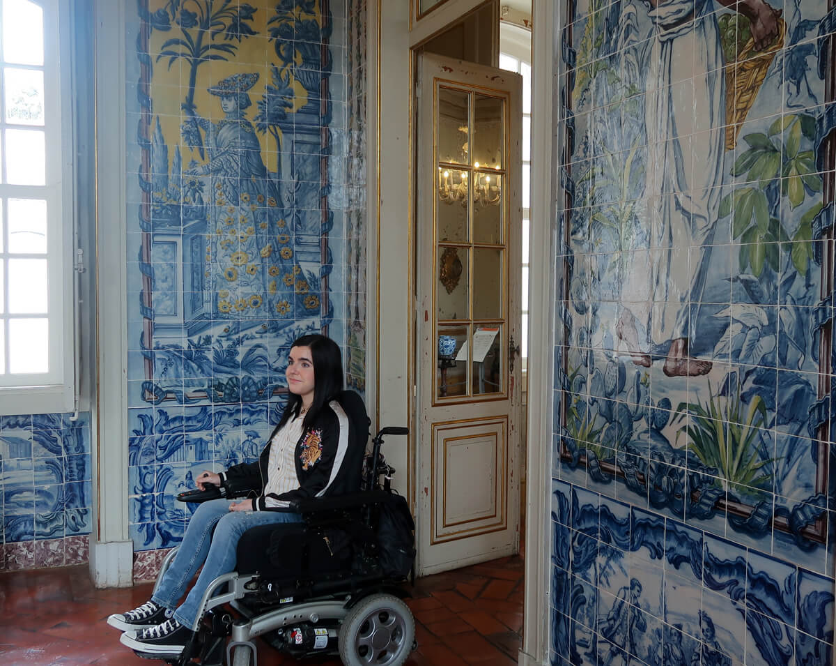 Emma sitting in a tiled room in Royal Palace of Queluz. The tiles on the wall are mainly blue with hints of yellow and green.