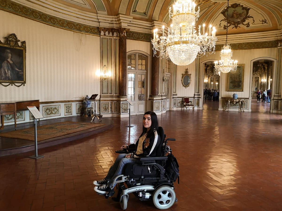 Emma, a wheelchair user is sitting in a large room with chandeliers in the Royal Palace of Queluz