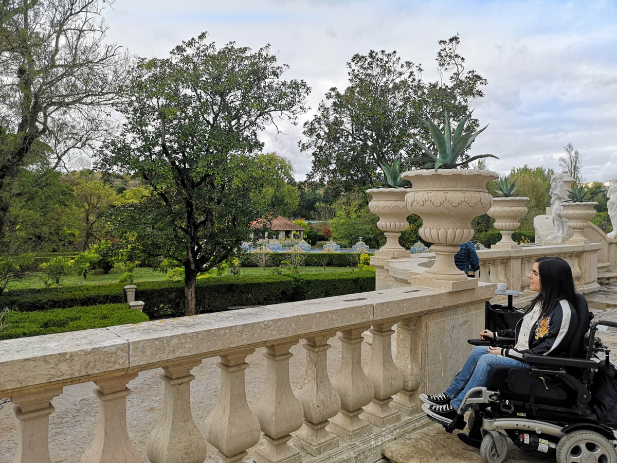 Emma, a power wheelchair user sitting outside admiring the gardens on a sunny day at Royal Palace of Queluz