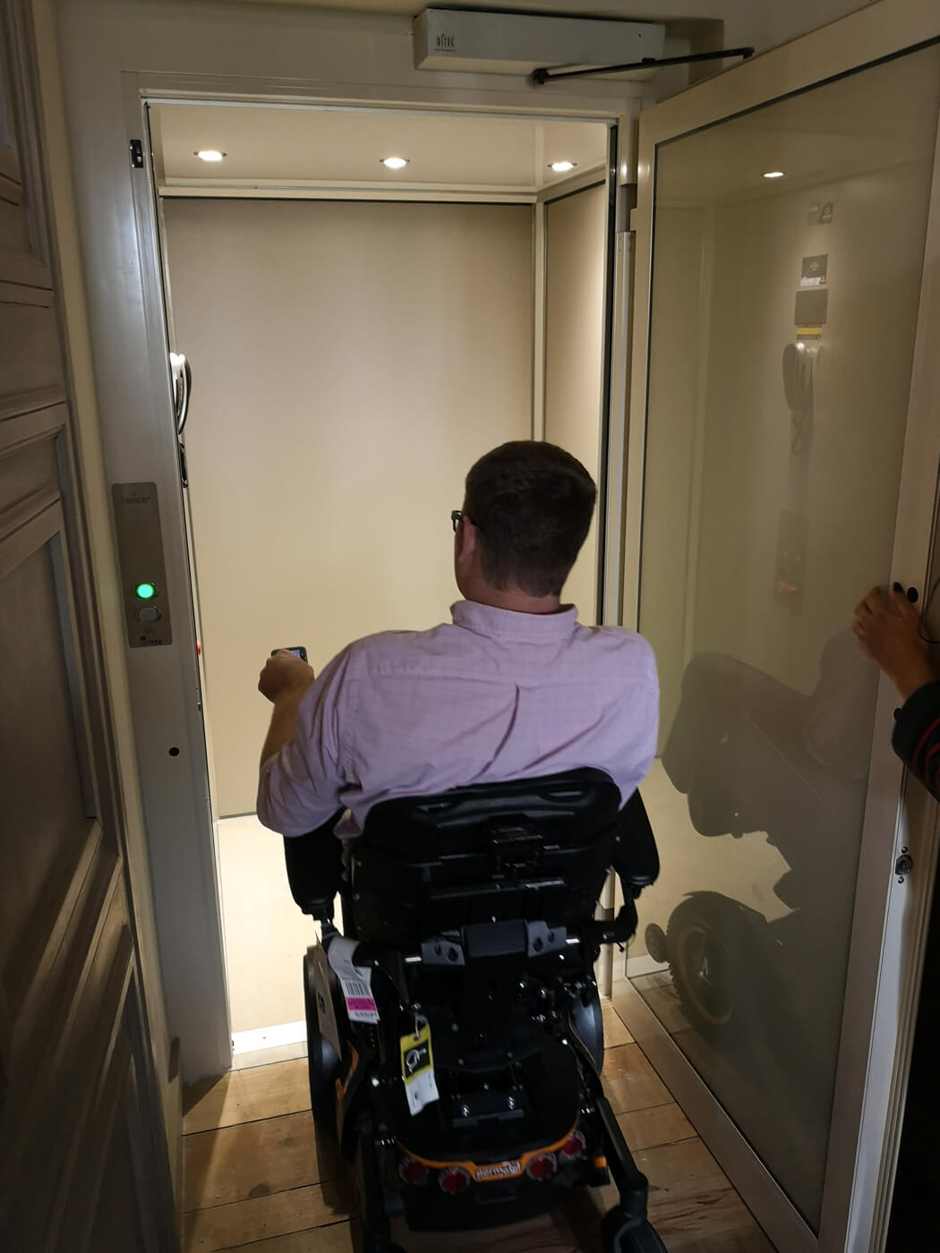 A man driving his power wheelchair into a lift at Royal Palace of Queluz