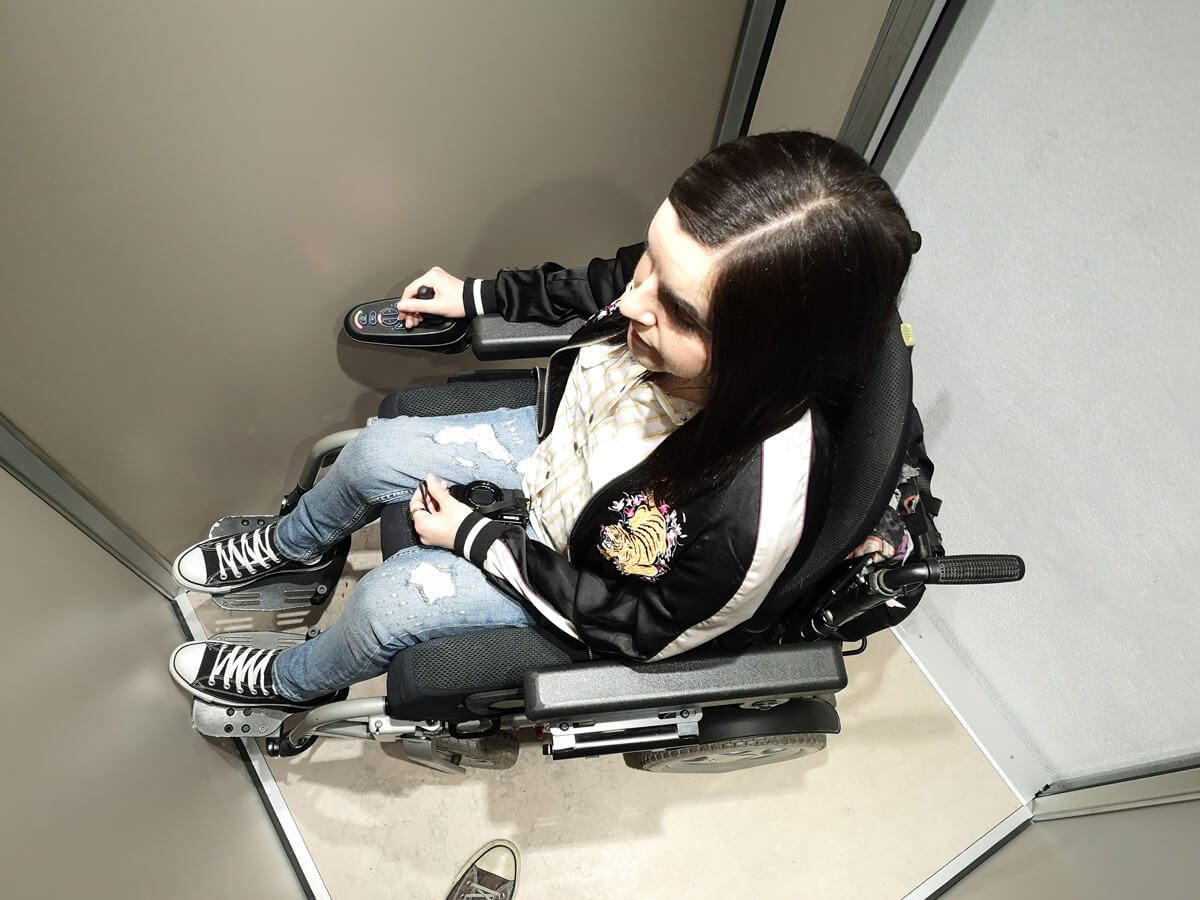 Emma, a power wheelchair user is sitting in a lift at Royal Palace of Queluz Portugal.