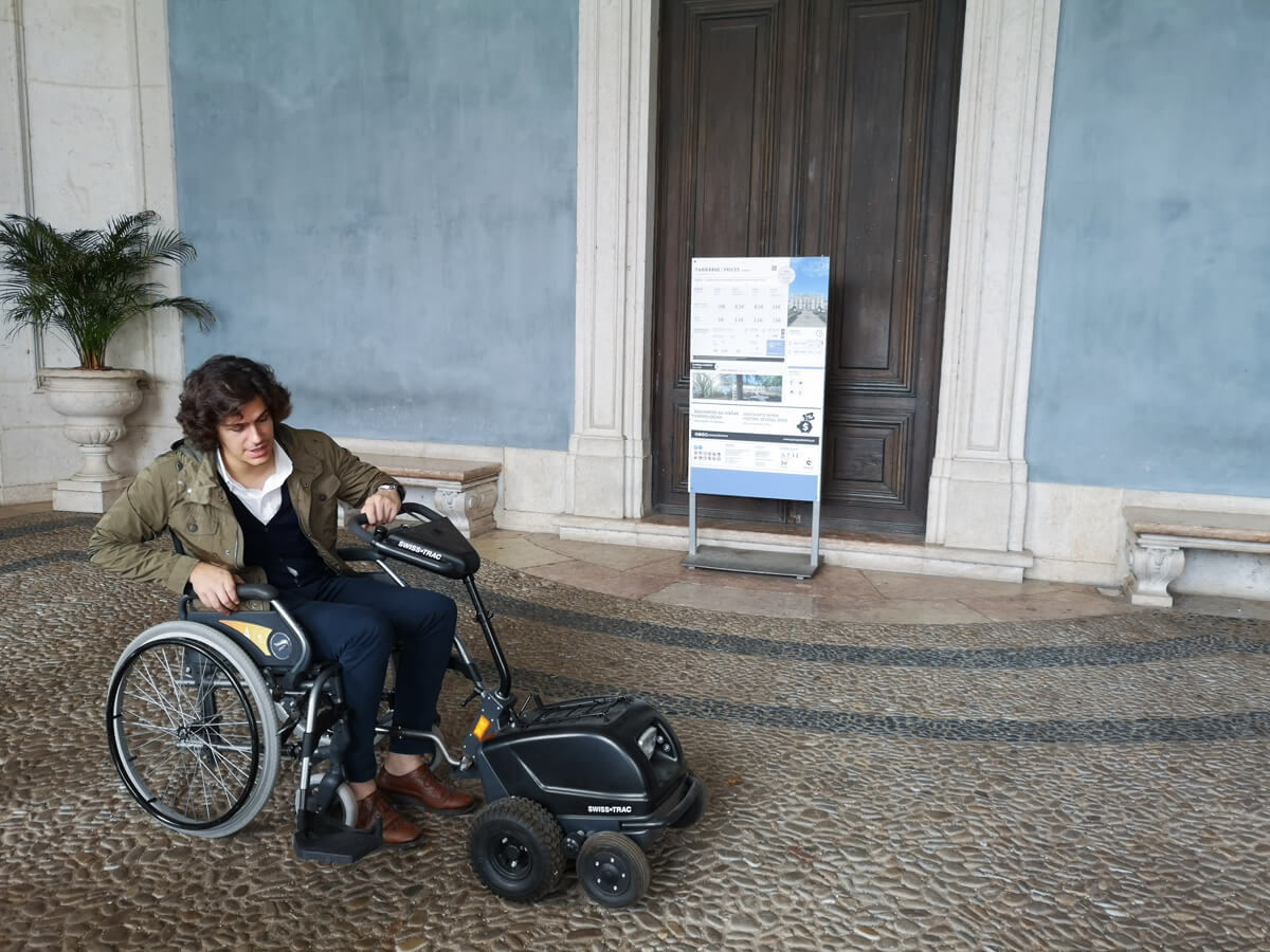 A man in a manual wheelchair with a motorised attachment on the front of the chair. The man works at Royal Palace of Queluz. He is showing what accessibility the Palace has.