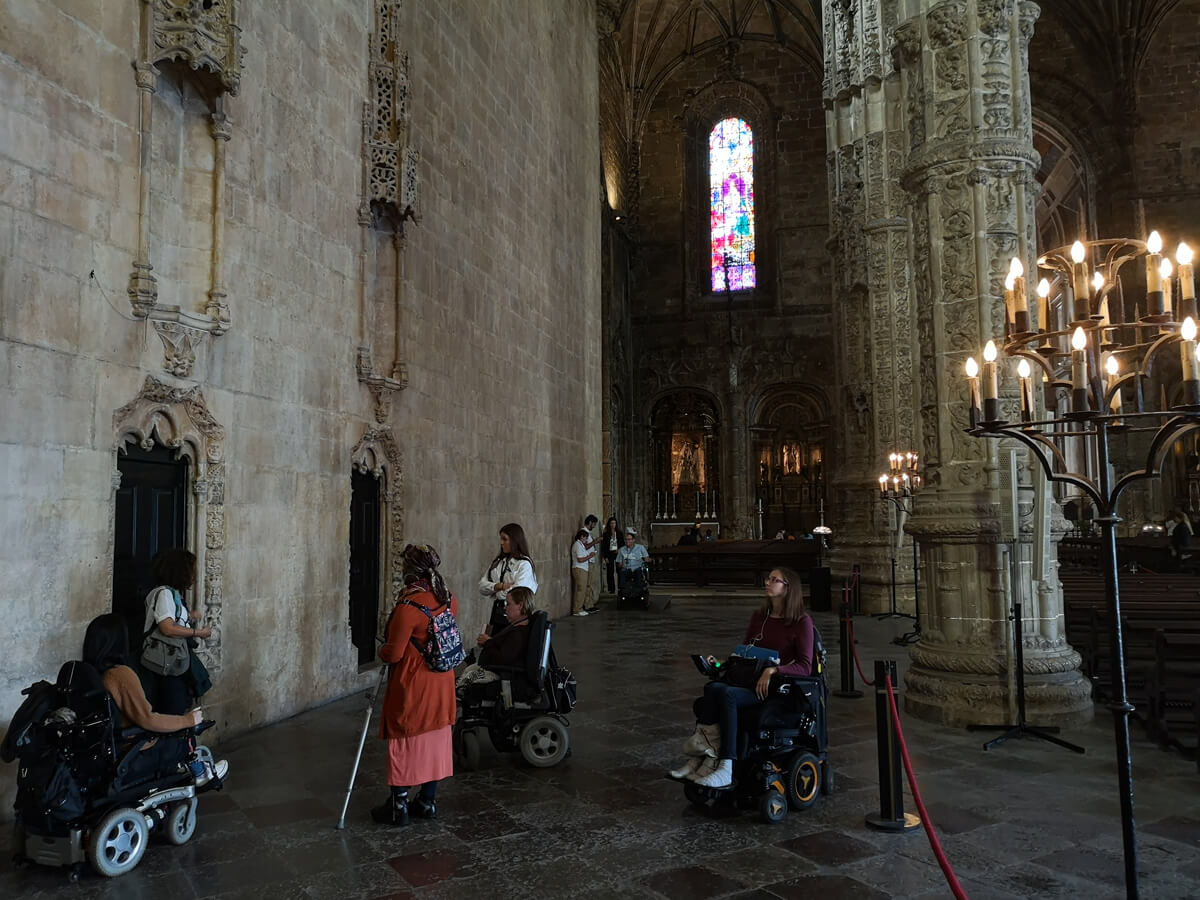 Emma and her tour group including wheelchair users being shown around inside Saint Jerome Monastery by their tour guide.