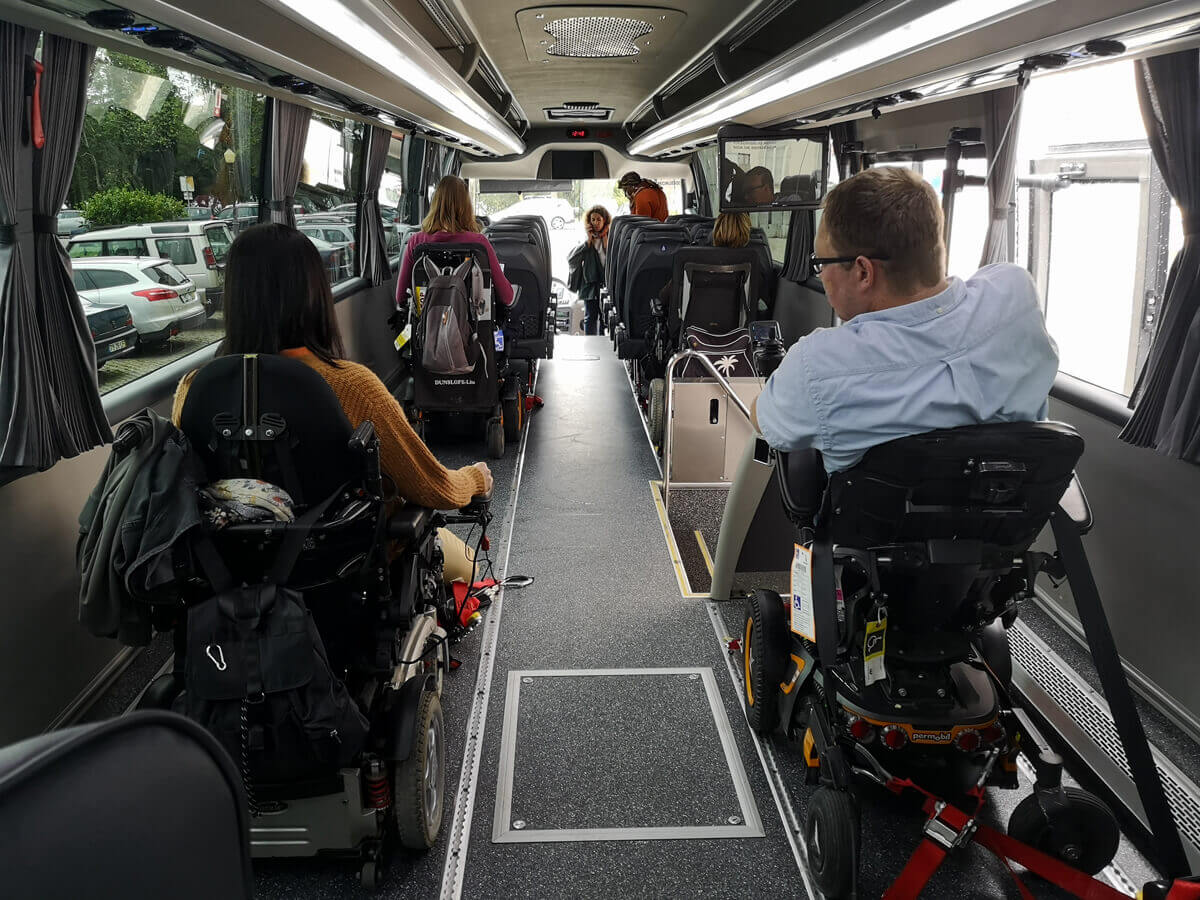 Emma and John (WheelchairTravel.org) sitting at the back of the Tourism For All bus.