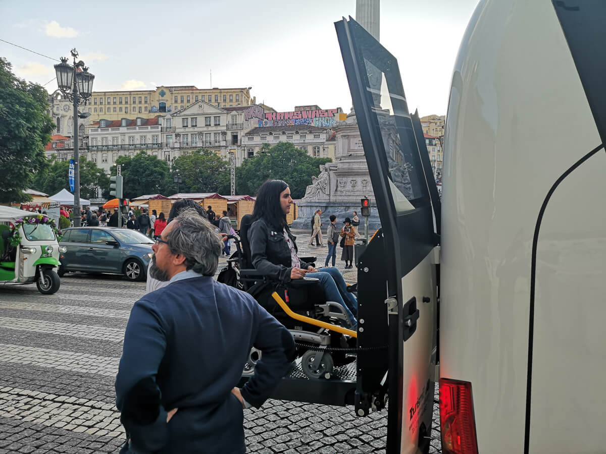 Emma exiting a large coach bus in the middle of downtown Lisbon.