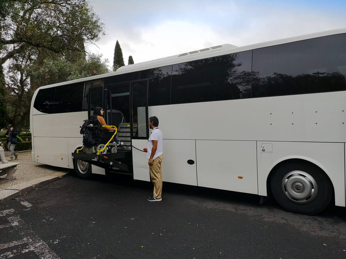 Emma exiting a large coach bus with the help of the driver.