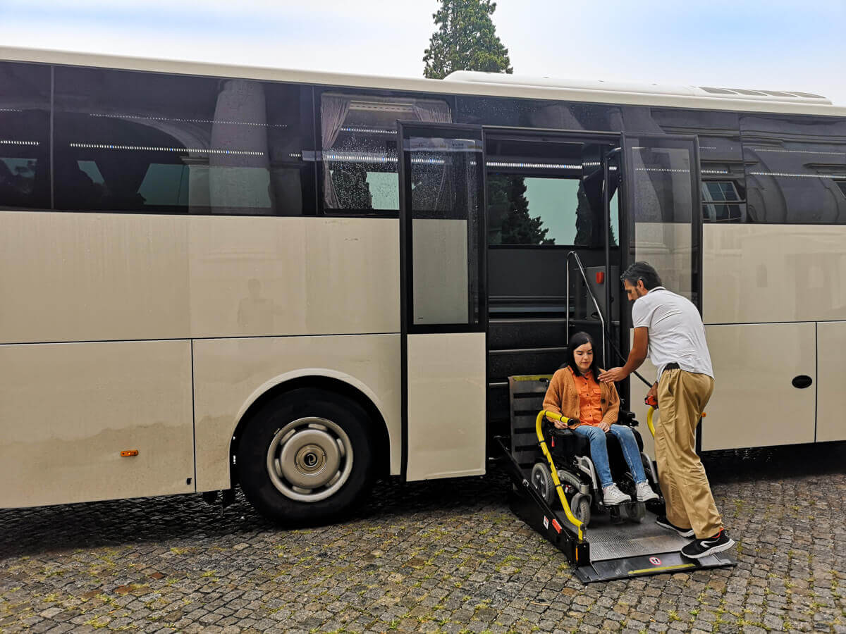 Emma sitting in her wheelchair on the platform lift exiting the bus. She is being supported by driver, Daniel who is placing his hand on her shoulder to prevent her from falling forward.
