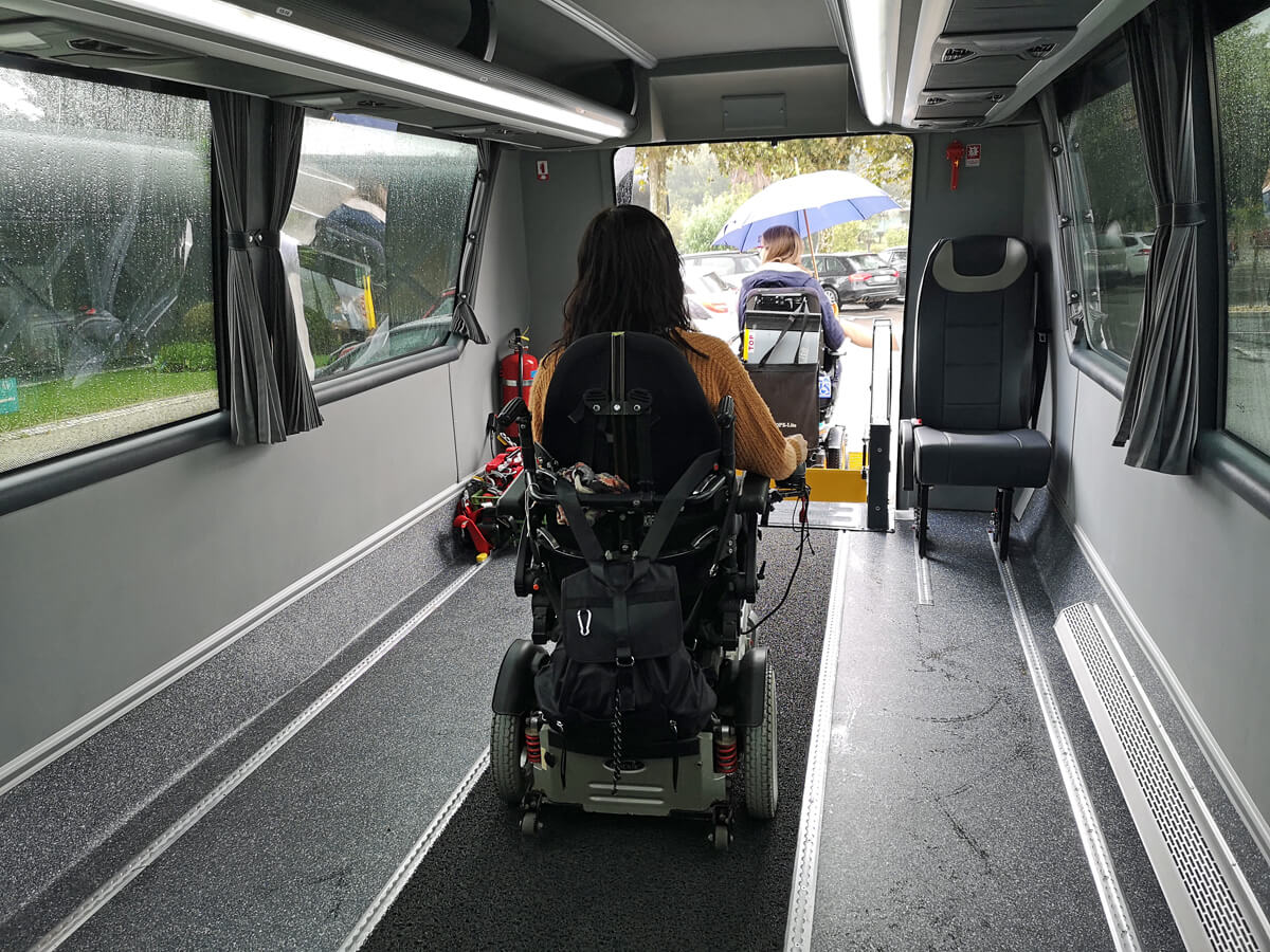 A back view of Emma driving her wheelchair to the back of the bus to exit via the electric wheelchair platform lift.