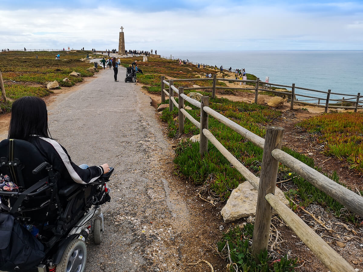 The back of Emma driving on the path towards the monument at Cabo da Roca. In the distance is the ocean and people walking around.