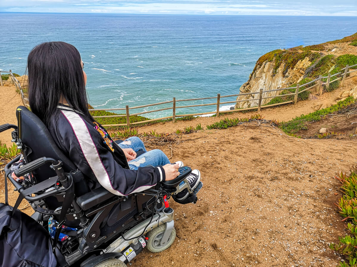 The back of Emma sitting in her power wheelchair. Emma is looking out at the view of the ocean behind her at Cabo da Roca.