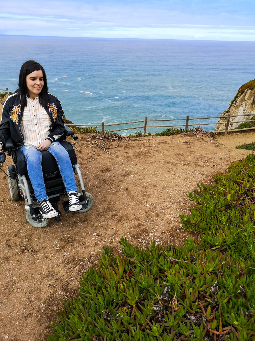 Emma sitting in her power wheelchair facing the camera. She is wearing blue skinny jeans, black converse shoes, a white and yellow striped shirt and black satin jacket with a tiger embroidery design. Emma is smiling and looking down with the view of the ocean behind her at Cabo da Roca.