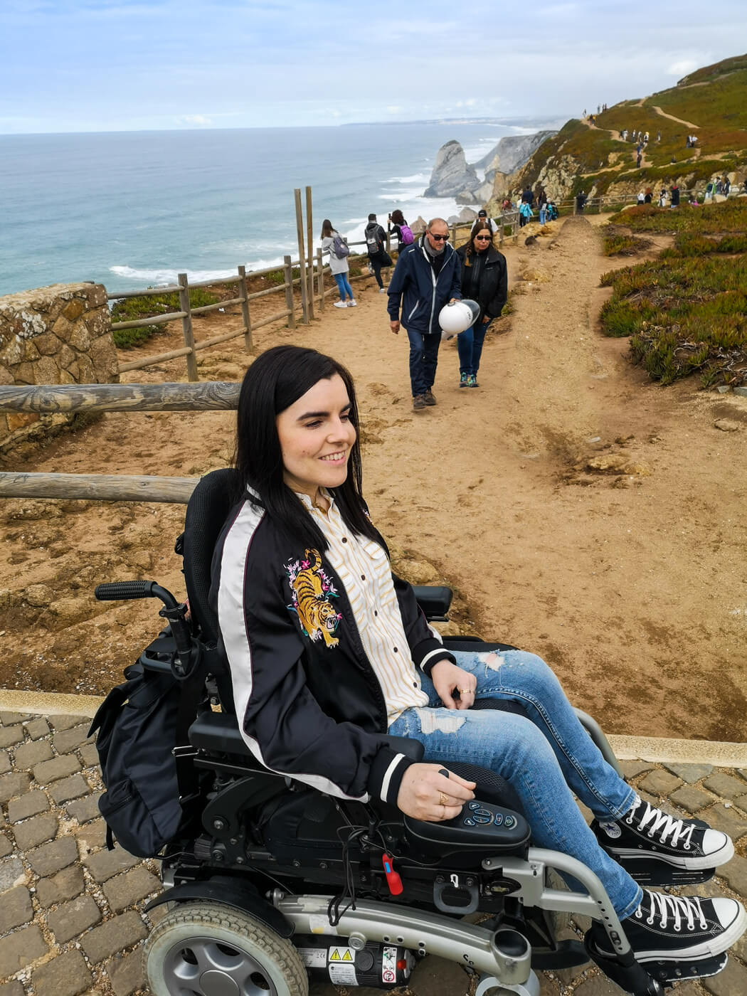 Emma sitting in her power wheelchair wearing blue skinny jeans, black converse shoes, a white and yellow striped shirt and black satin jacket with a tiger embroidery design. Emma is smiling with the view of the ocean behind her at Cabo da Roca.