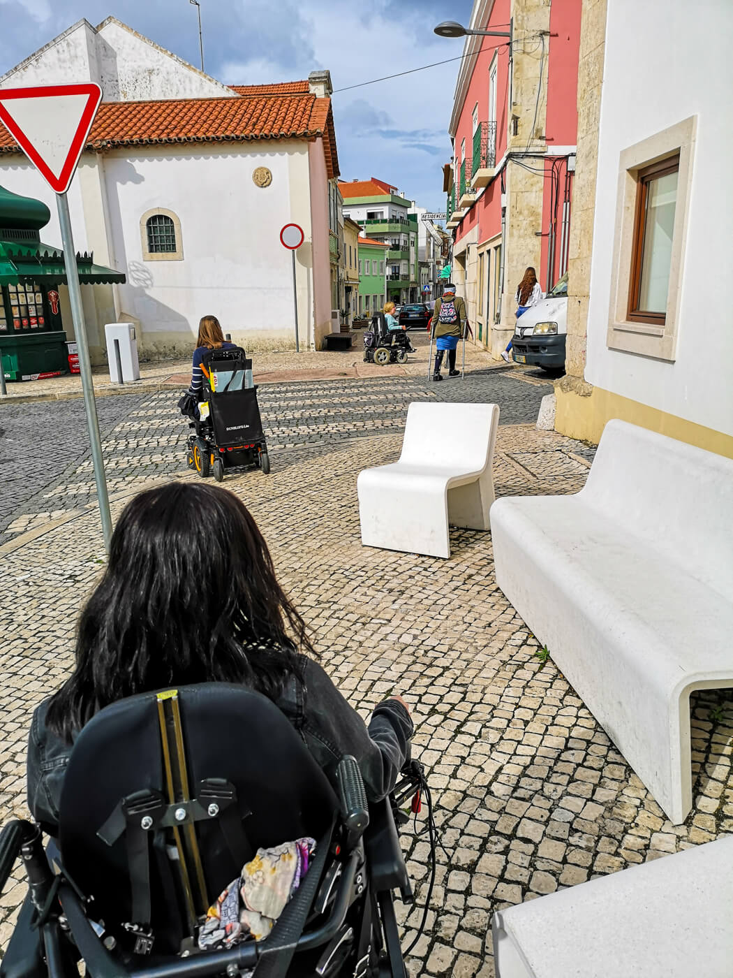 A view of Emma from the back. She is driving her wheelchair across cobblestones in the town of Caldas da Rainha. In front of Emma is two wheelchair users and a woman walking with crutches. They are also part of the tour group