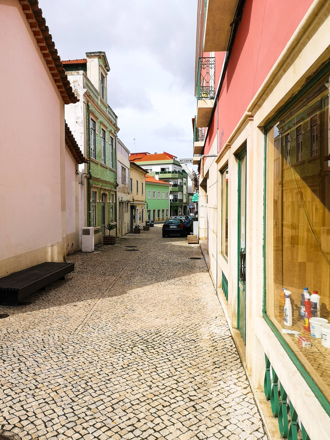 A cobblestone lane in the Caldas da Rainha town of Portugal. The buildings are painted baby pink and green.