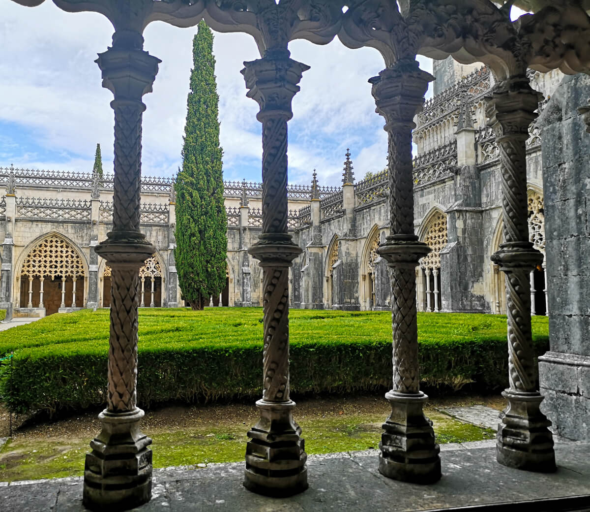 A view looking out to the gardens through the molded columns inside Batalha Monastery