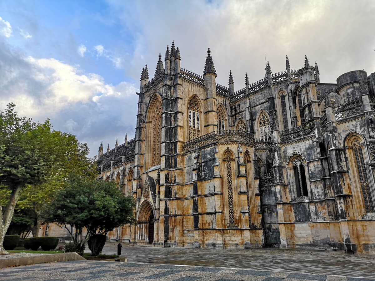 The exterior of Batalha Monastery on a bright but cloudy day.