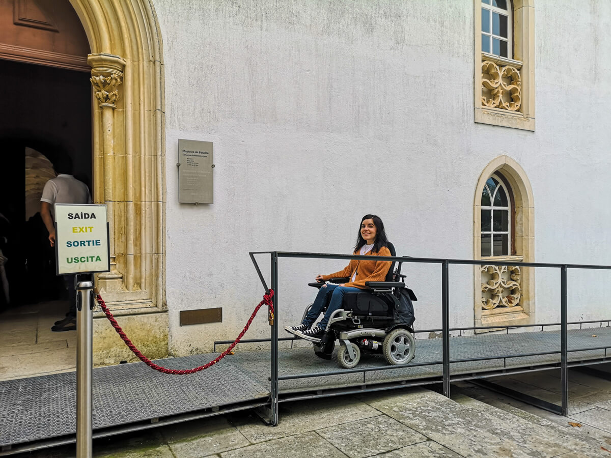 Emma driving up a wheelchair ramp to enter the Batalha Monastery.